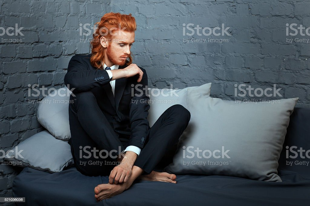 Metrosexual man sitting on the couch. stock photo