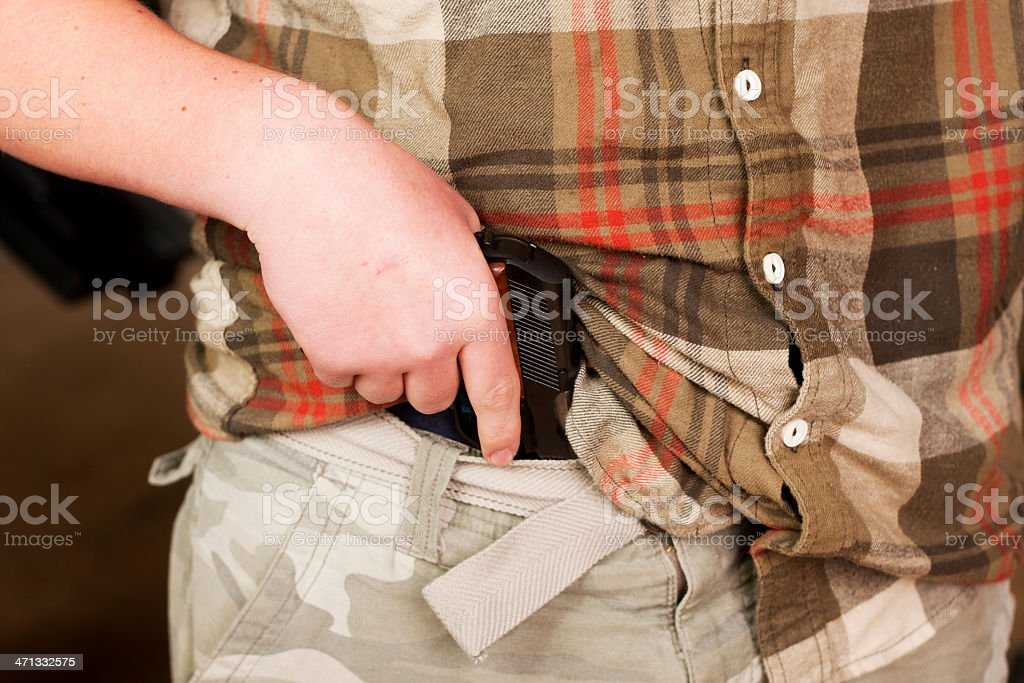 Mexican Carry - Concealed Firearm Drawn From Waistband stock photo