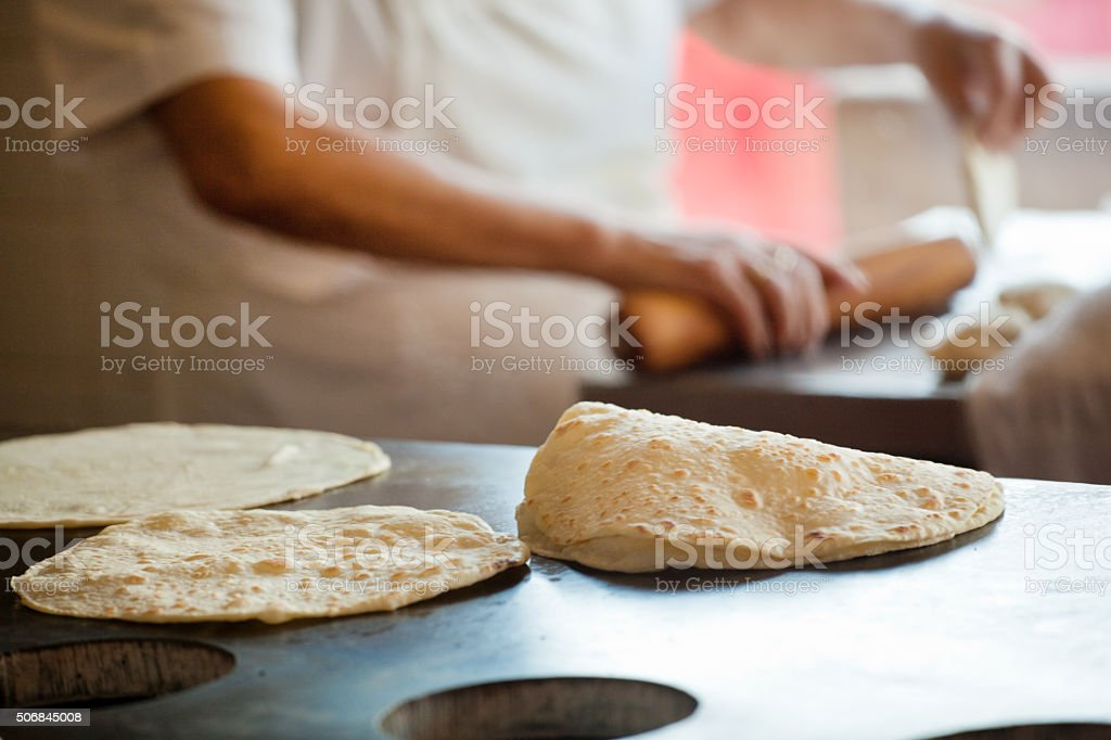 Mexican Chef Rolling, Frying Flour Tortillas in Restaurant Commercial Kitchen stock photo