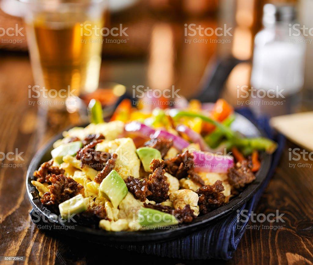 mexican chorizo scrambled eggs in fajita skillet stock photo