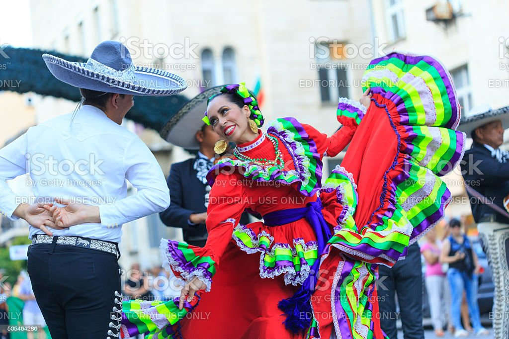 Mexican couple in traditional costumes dancing on street stock photo