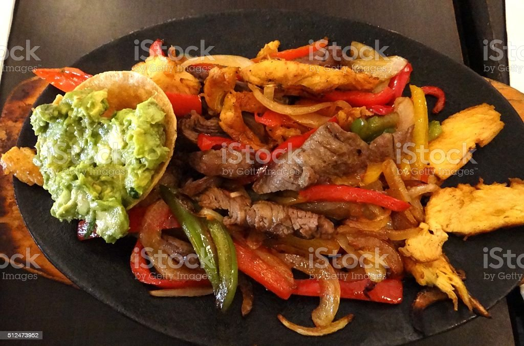 Mexican fajitas beef and chicken dish with guacamole stock photo