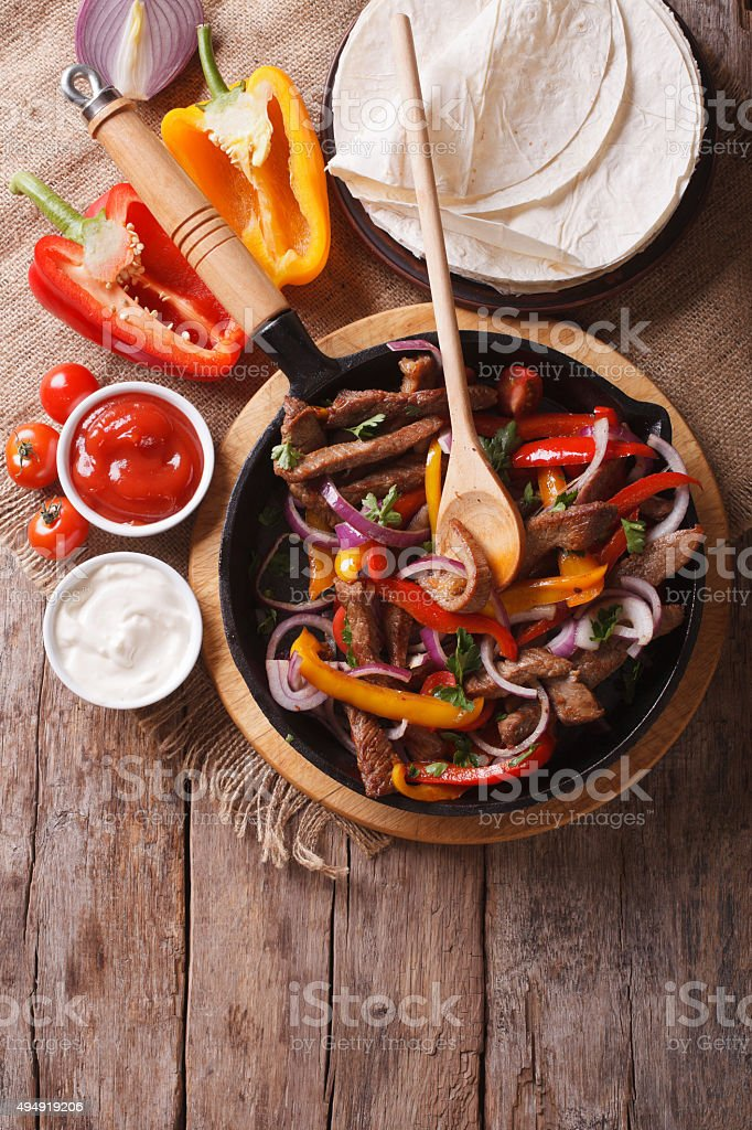 Mexican fajitas on a table, rustic style vertical top view stock photo