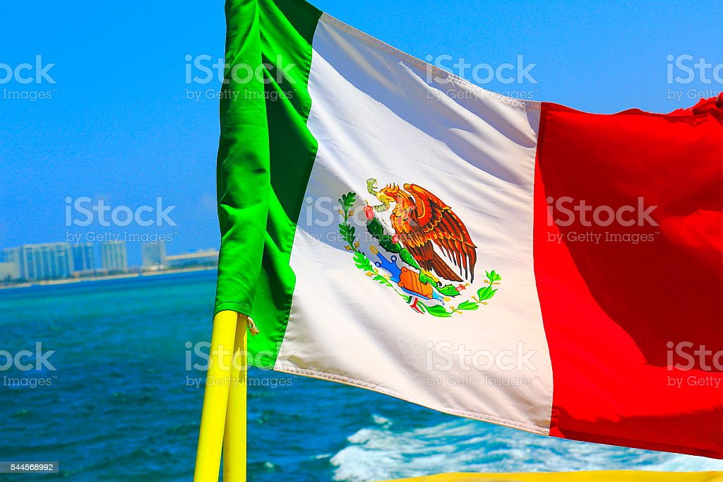 Mexican Flag winding over caribbean turquoise sea on ship cruise stock photo