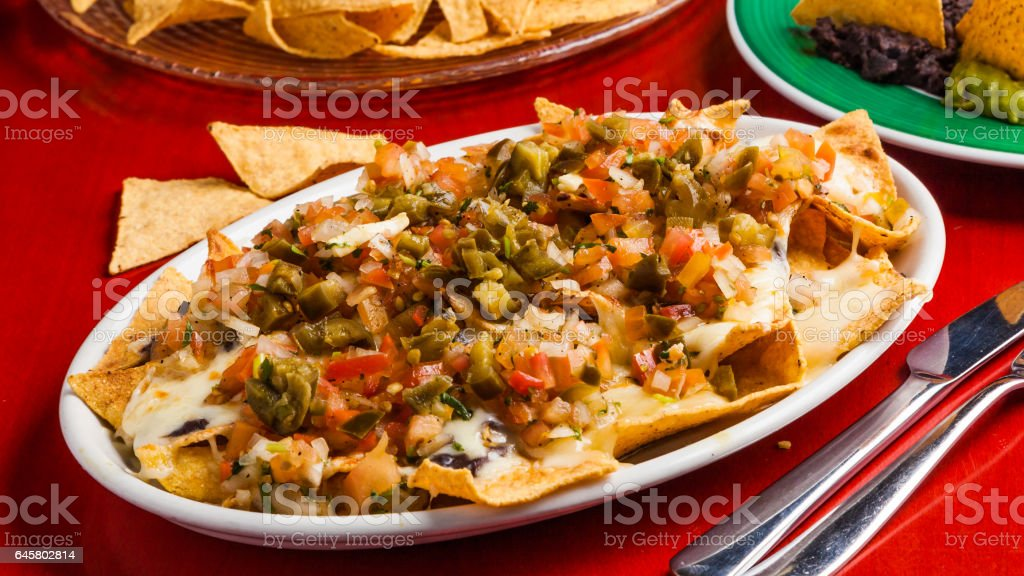 Mexican food: nachos with melted cheese, tomato and peppers. stock photo