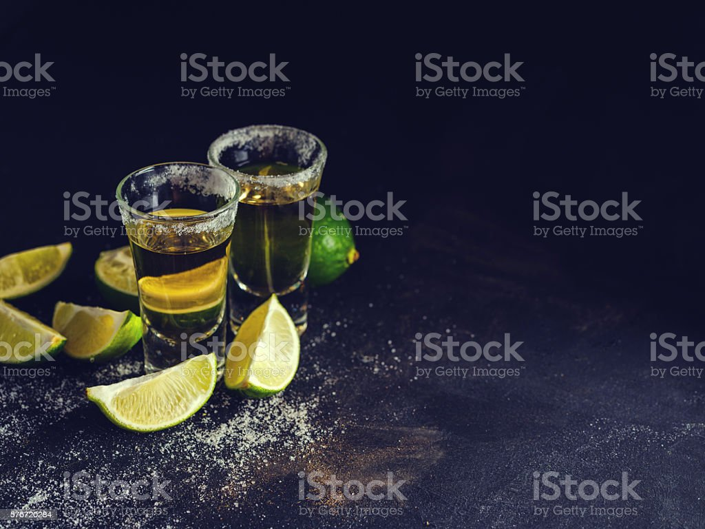 Mexican Gold Tequila with lime and salt on dark table. stock photo