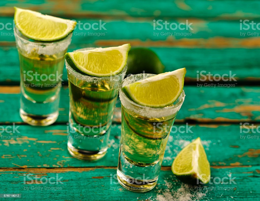 Mexican Gold Tequila with lime and salt on wooden table stock photo