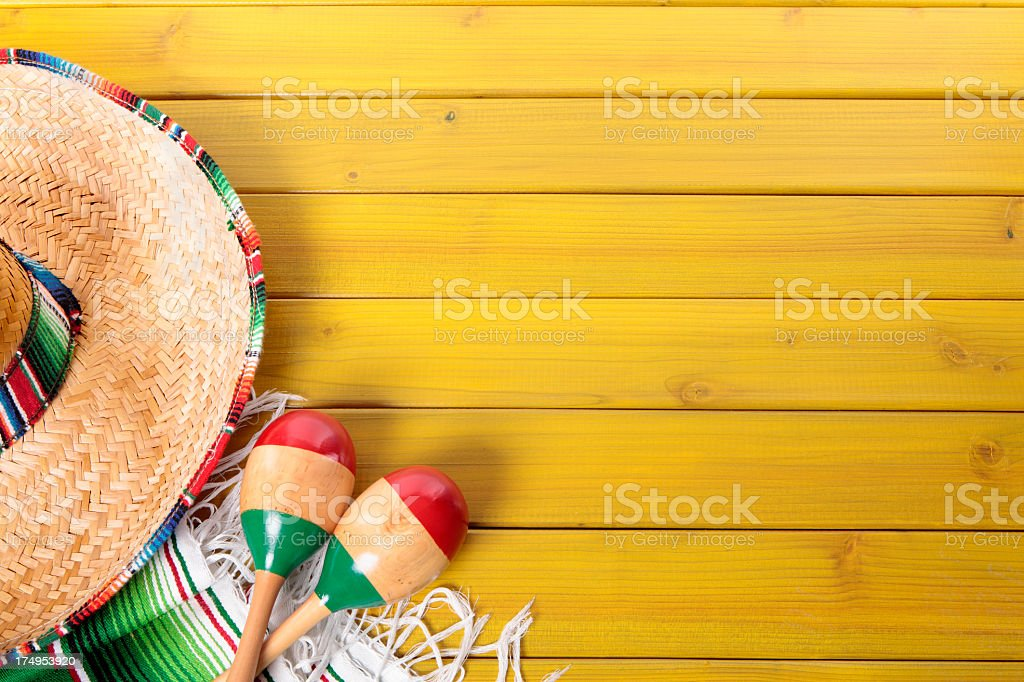 Mexican hat, maracas and poncho on yellow wooden surface stock photo