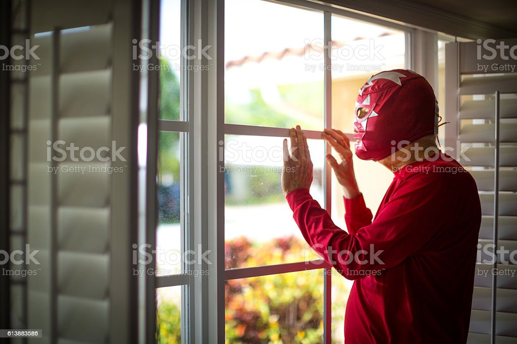 Mexican luchador looking thru the windows stock photo