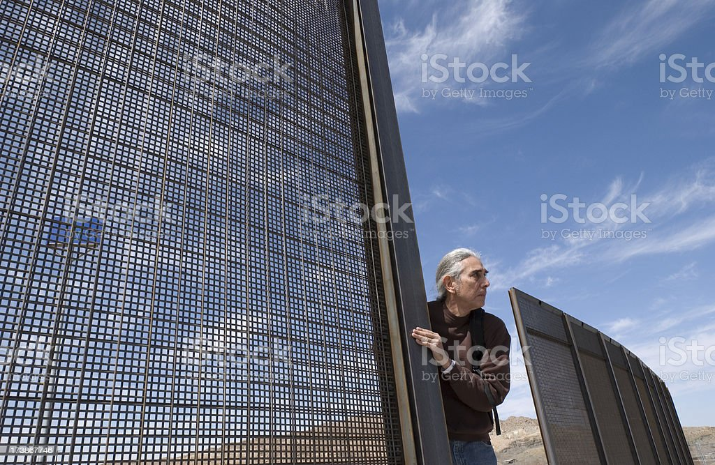 Mexican Male Crossing Border Fence Horizontal royalty-free stock photo