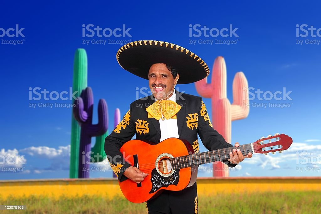 Mexican mariachi charro playing guitar in cactus royalty-free stock photo