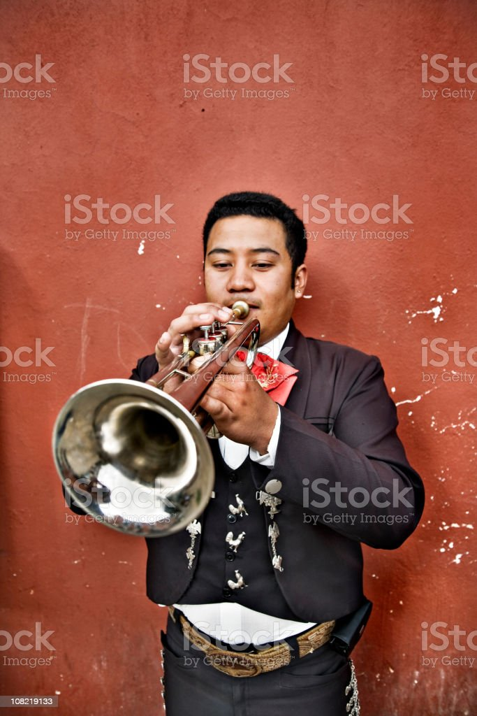 Mexican Mariachi Man Playing Trumpet Against Wall royalty-free stock photo