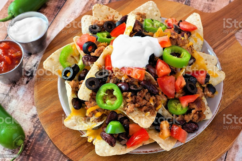 Mexican nacho chips on a wooden paddle board stock photo