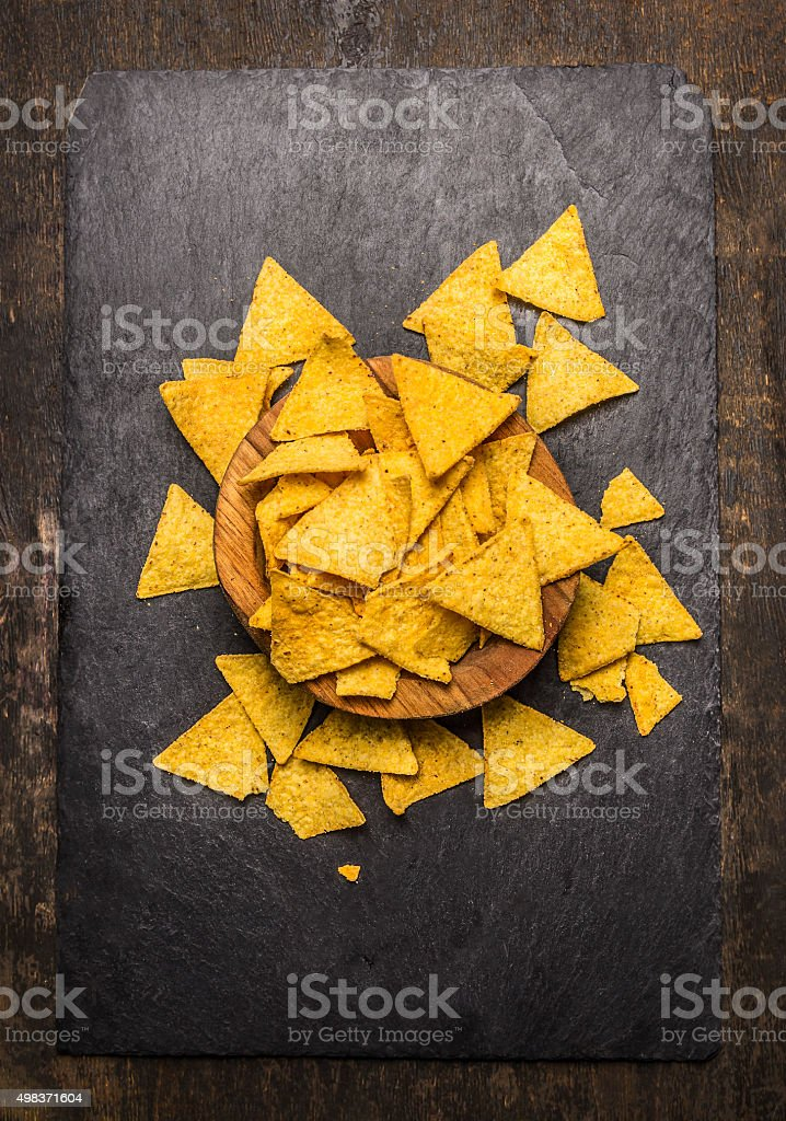 Mexican nacho in a wooden bowl rustic background top view stock photo