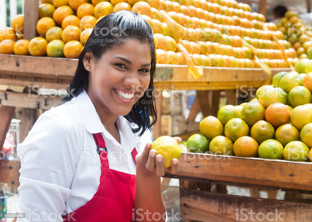 Mexican saleswoman offering oranges on a farmers market stock photo
