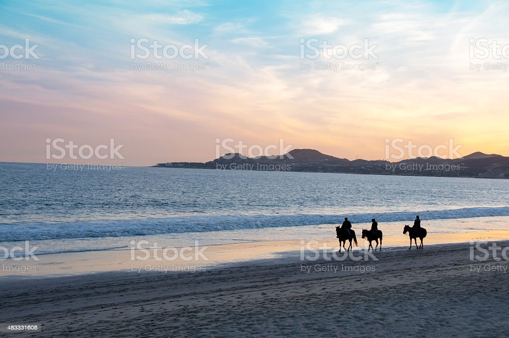 Mexican sunset near Cabo san Lucas with man and horses stock photo