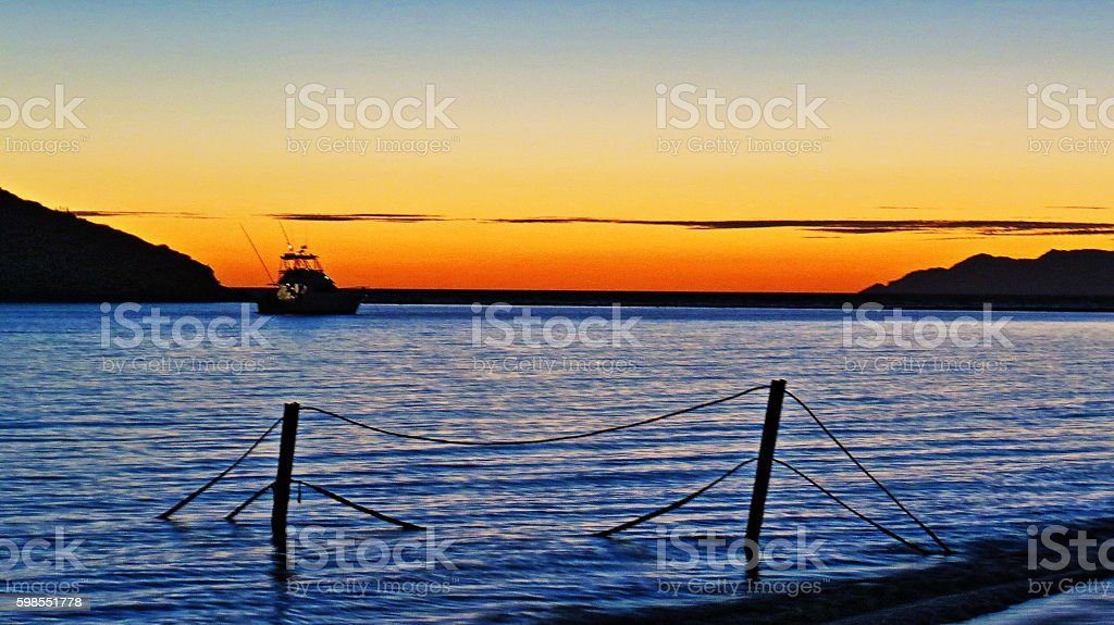 Mexican sunset with fishing boat stock photo