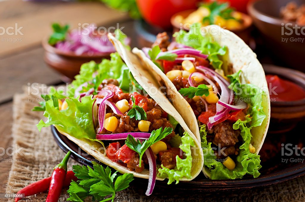 Mexican tacos on flour tortillas with corn salsa and meat stock photo