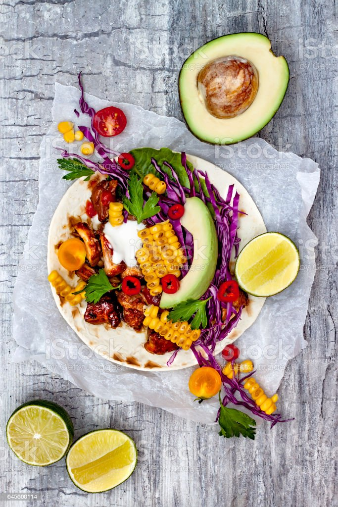 Mexican tacos with avocado, slow cooked meat, grilled corn, red cabbage slaw and chili salsa on rustic stone table. Recipe for Cinco de Mayo party. stock photo