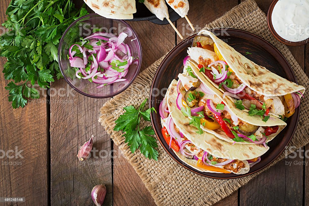 Mexican tacos with chicken, grilled vegetables and red onion. stock photo