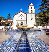 A Mexican tile fountain in front of a white chapel