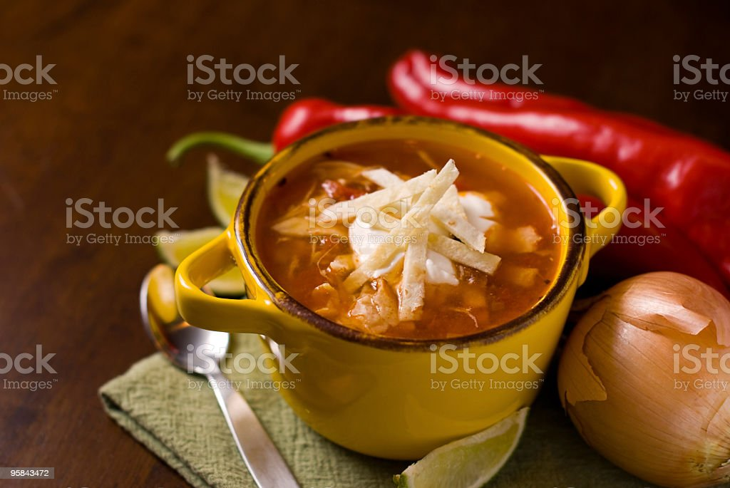 A Mexican tortilla soup in a bowl on a wooden table royalty-free stock photo
