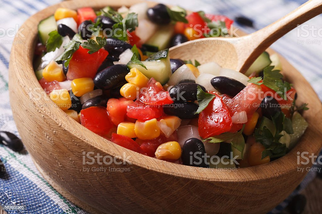 Mexican vegetable salad macro in a wooden plate. horizontal stock photo
