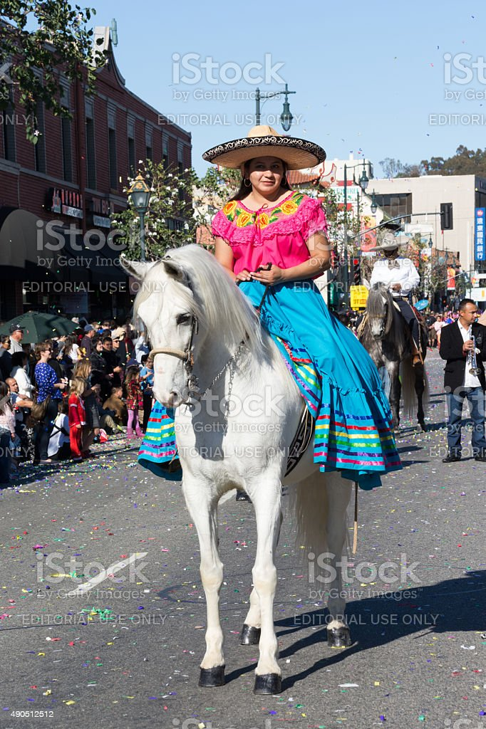 Mexican Woman on a horse  during the Golden Dragon Parade stock photo