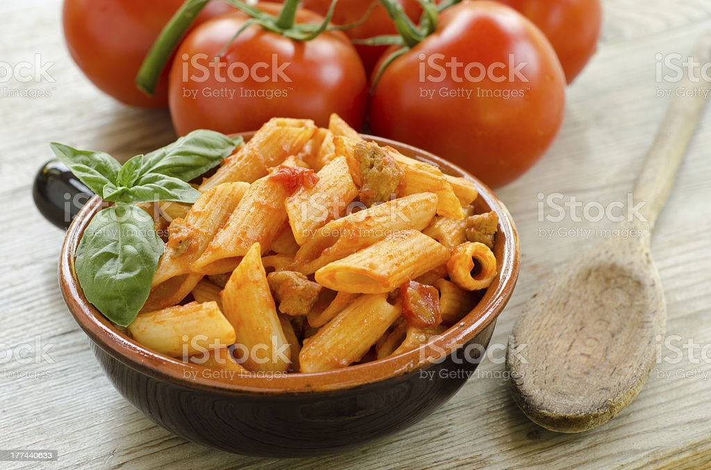 Mezze penne with tomato sauce and meat in a bowl stock photo