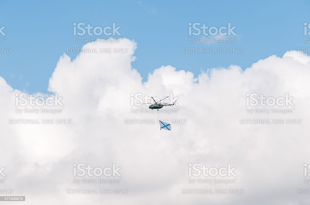 Mi-8 helicopter with giant Russian Navy flag against sky background royalty-free stock photo