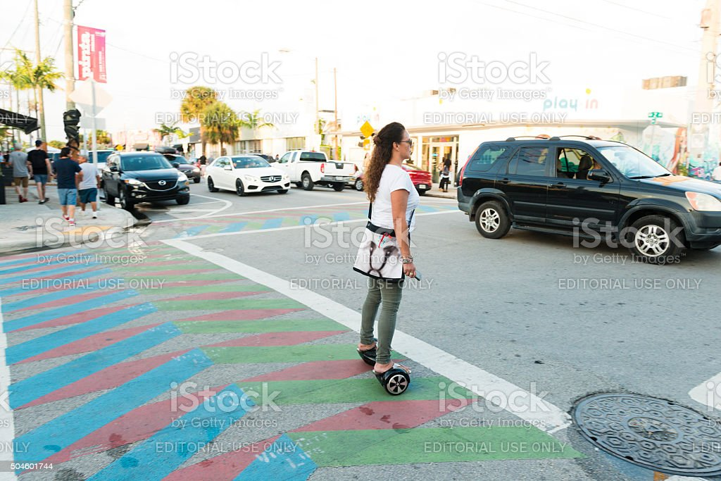 Miami Wynwood Woman Crosses Street on Hoverboard stock photo
