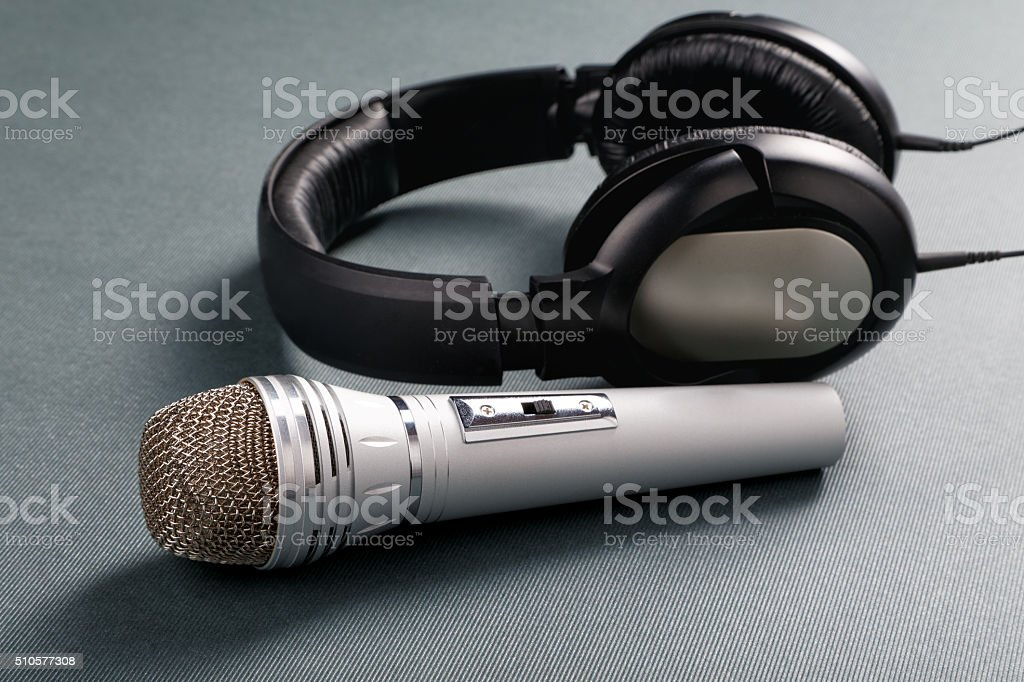 Microphone and ear-phones on a table stock photo