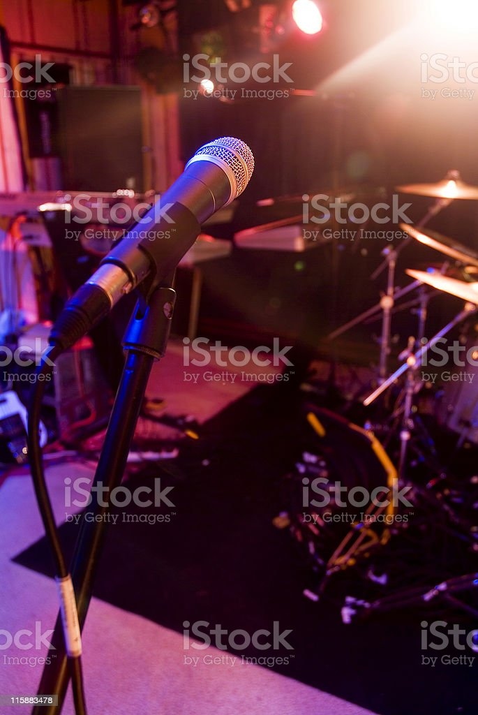 Microphone at a venue with drum kit in background royalty-free stock photo