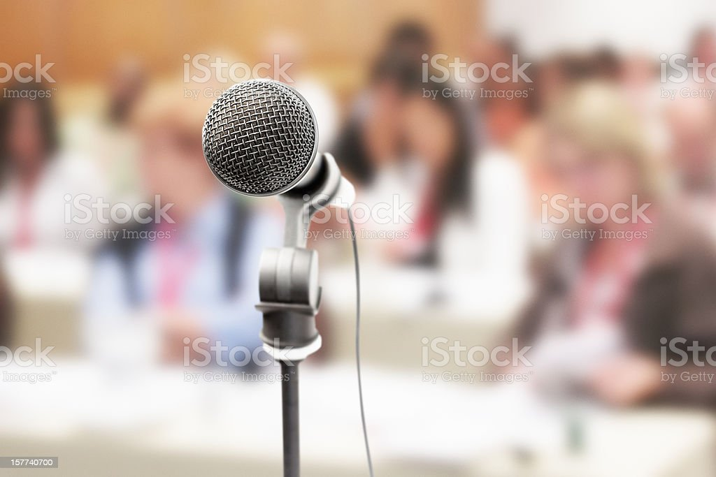 Microphone awaits speaker as audience waits in background royalty-free stock photo