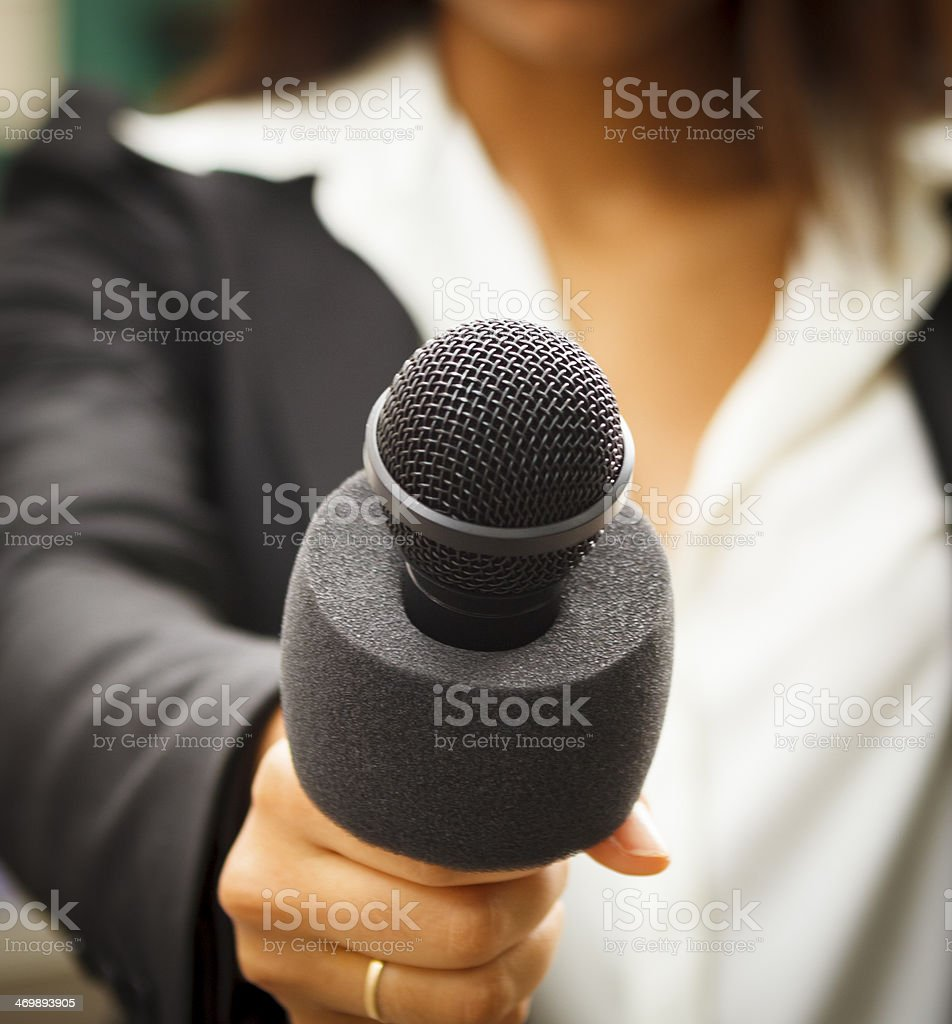 Microphone Held by Female Reporter Close-up stock photo