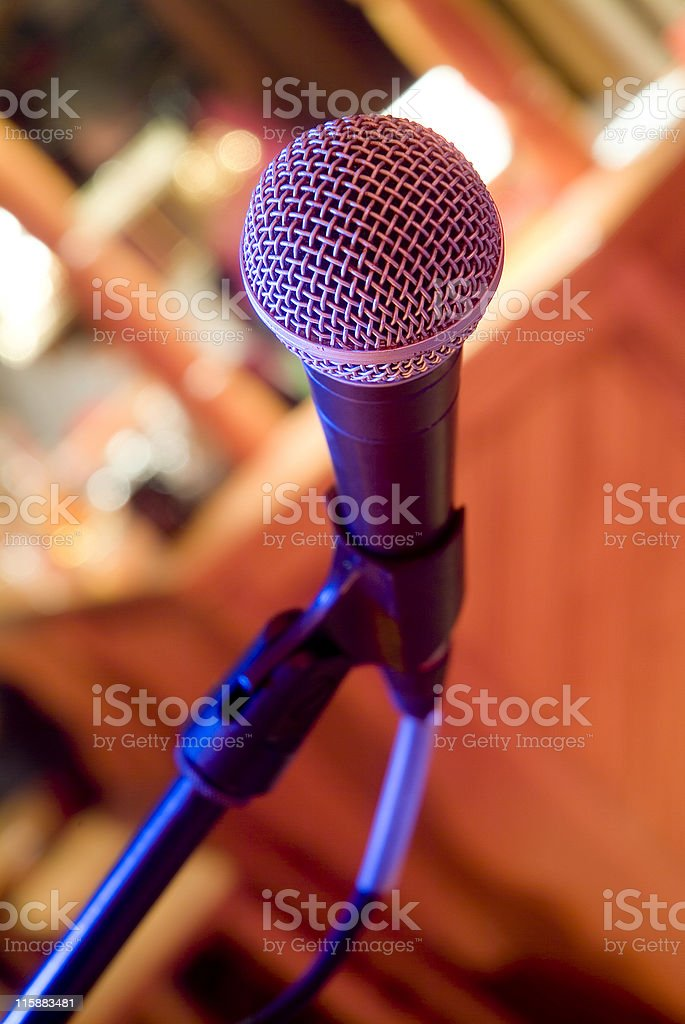 Microphone in a venue with background out of focus royalty-free stock photo