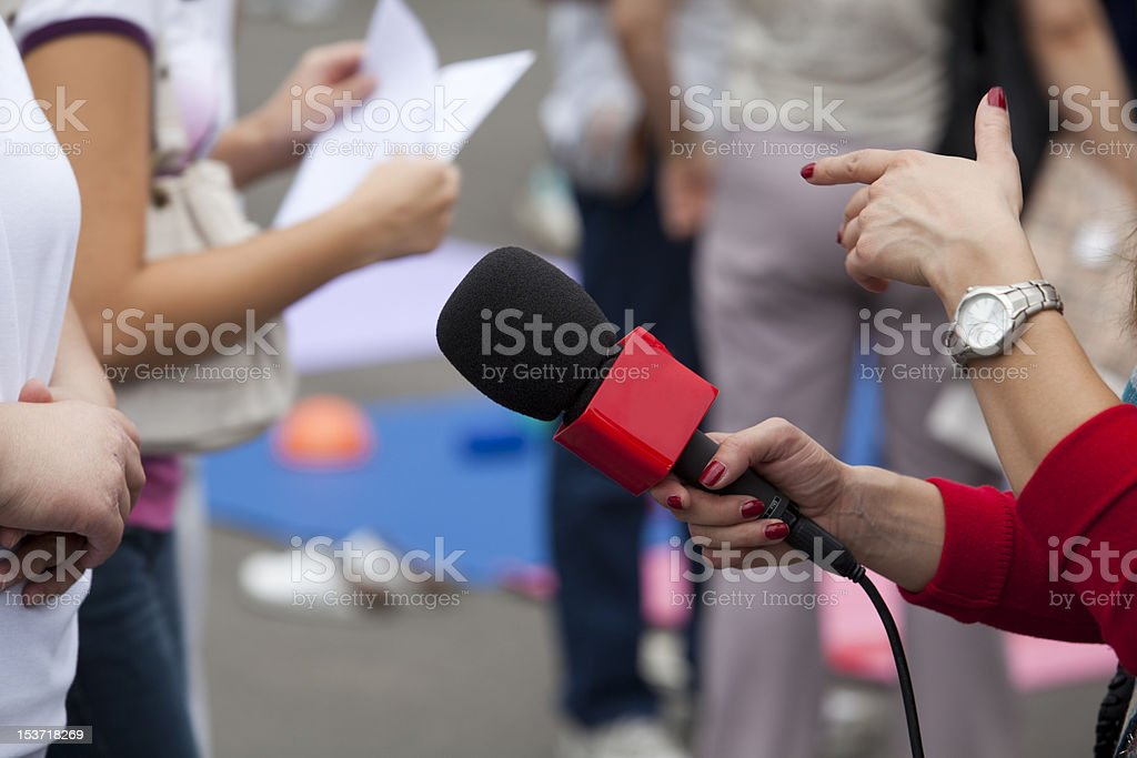Microphone in female reporter's hand royalty-free stock photo