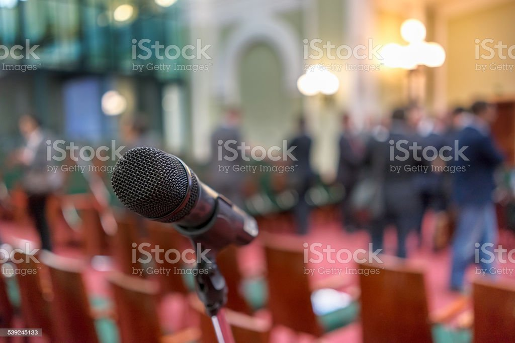 Microphone in focus against blurred chairs and standing talking audience stock photo