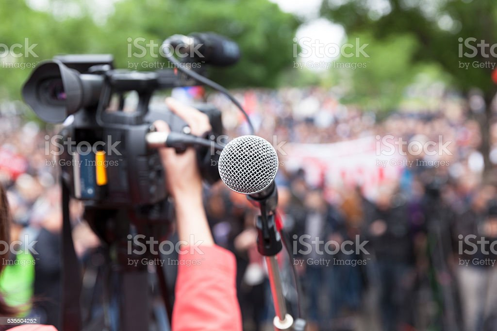 Microphone in focus against blurred crowd. Filming protest. stock photo