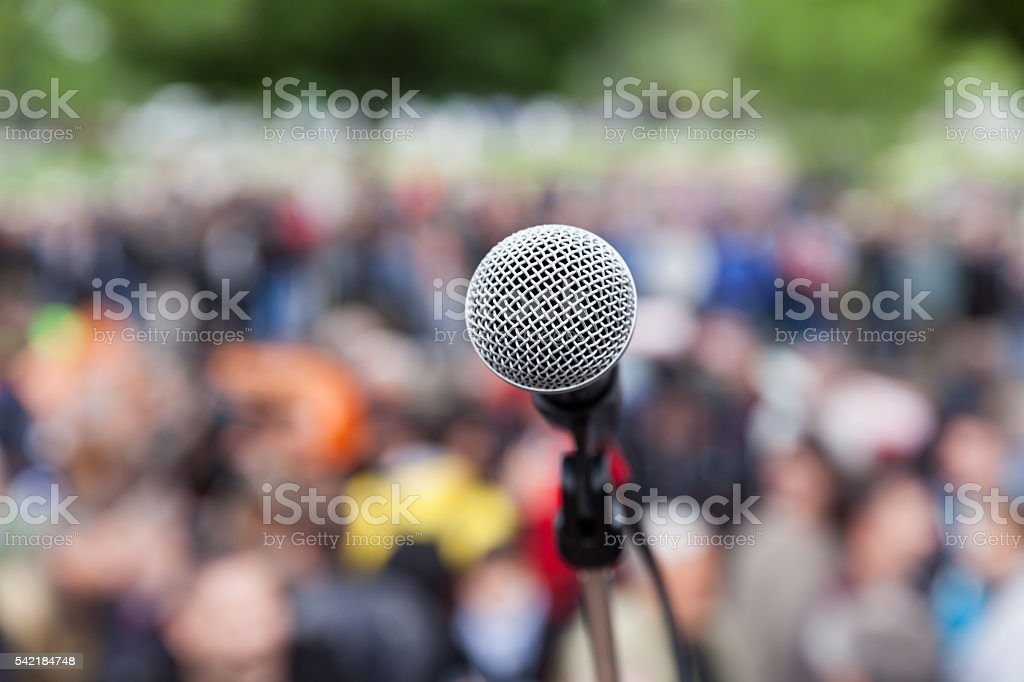 Microphone in focus against blurred crowd. Protest. stock photo