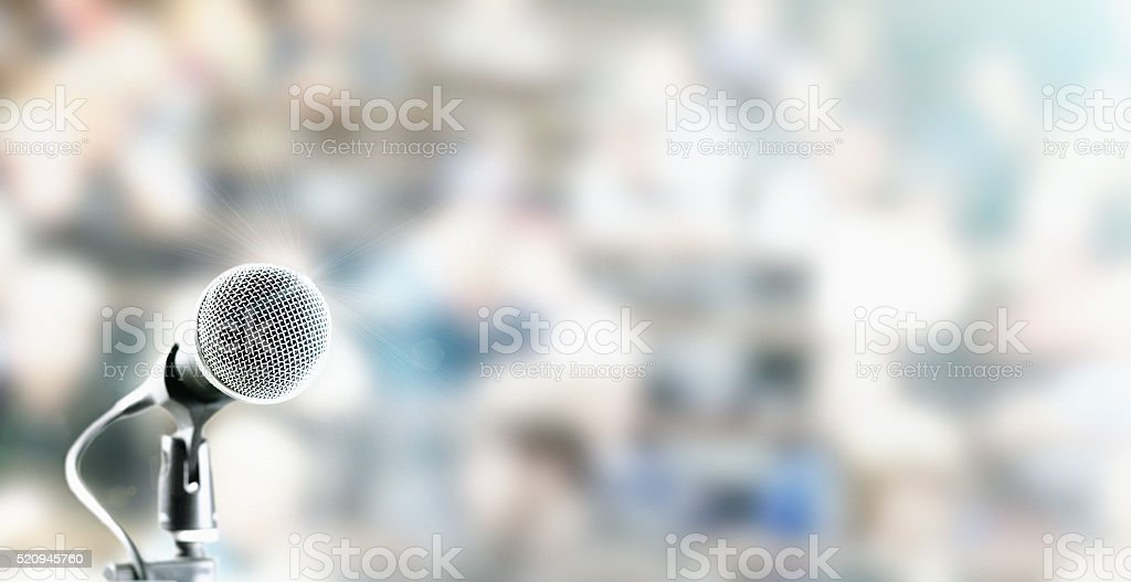 Microphone  in front of out-of-focus audience stock photo