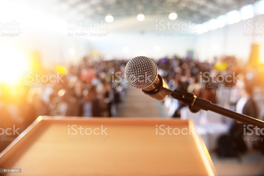 Microphone in front of podium with crowd in the background stock photo