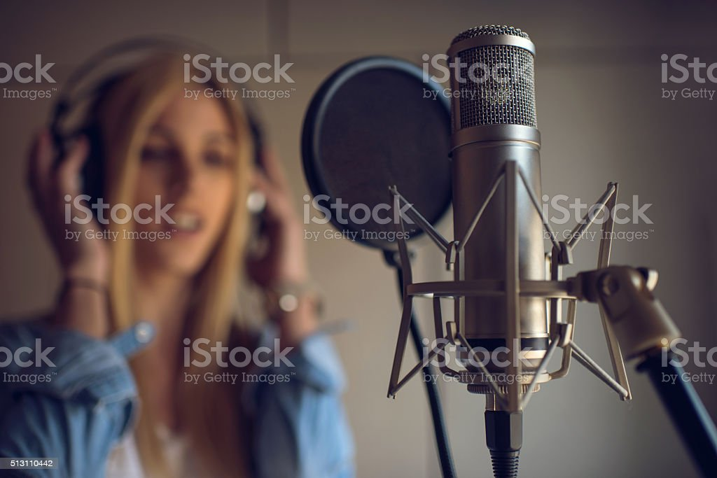 Microphone in recording studio with singer in the background. stock photo