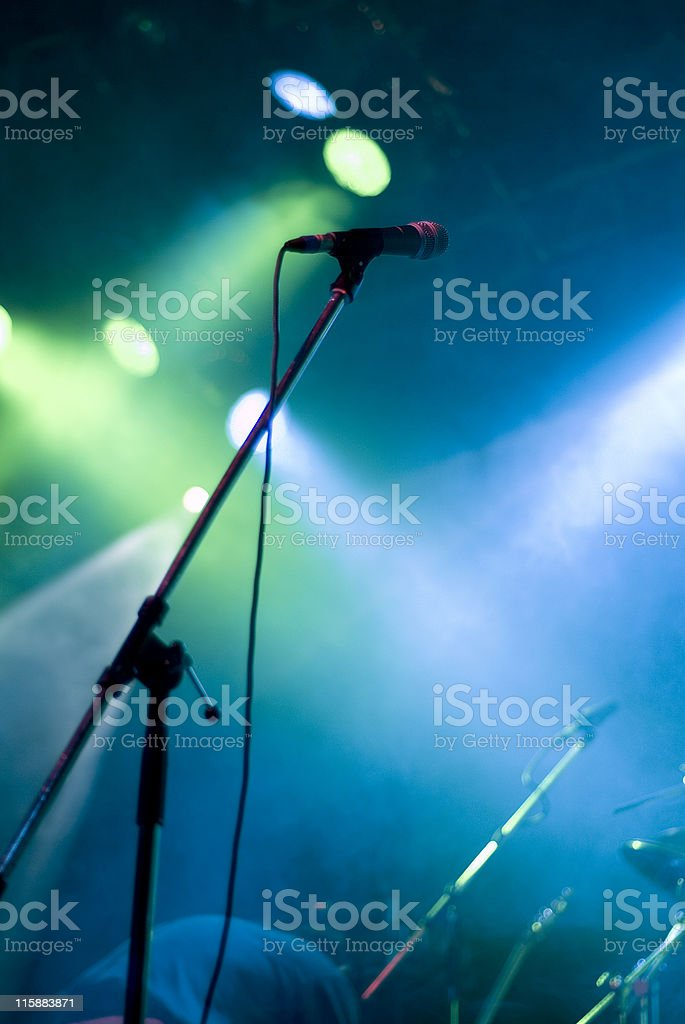 Microphone on a large stage with blue and green lighting stock photo