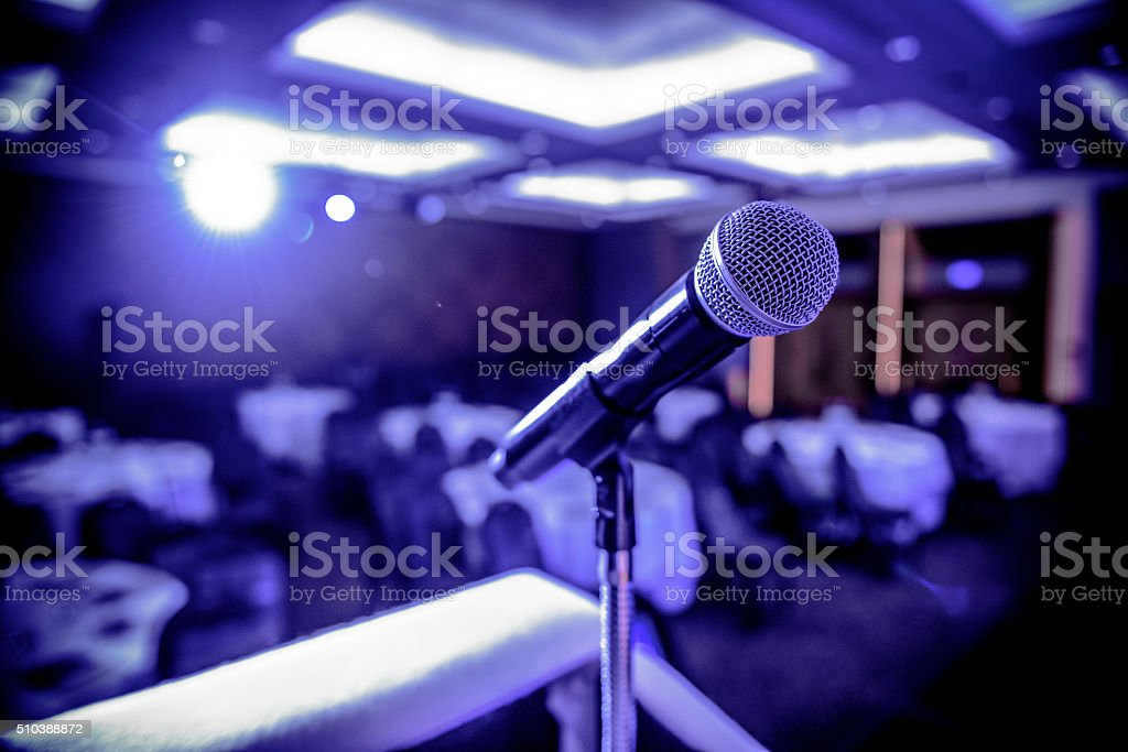 Close up of microphone backlit by stage light at a business...