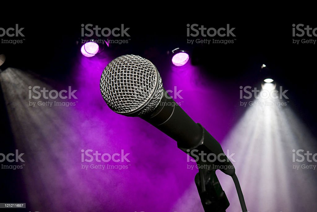 Microphone on stand lit with stage lighting and smoke royalty-free stock photo