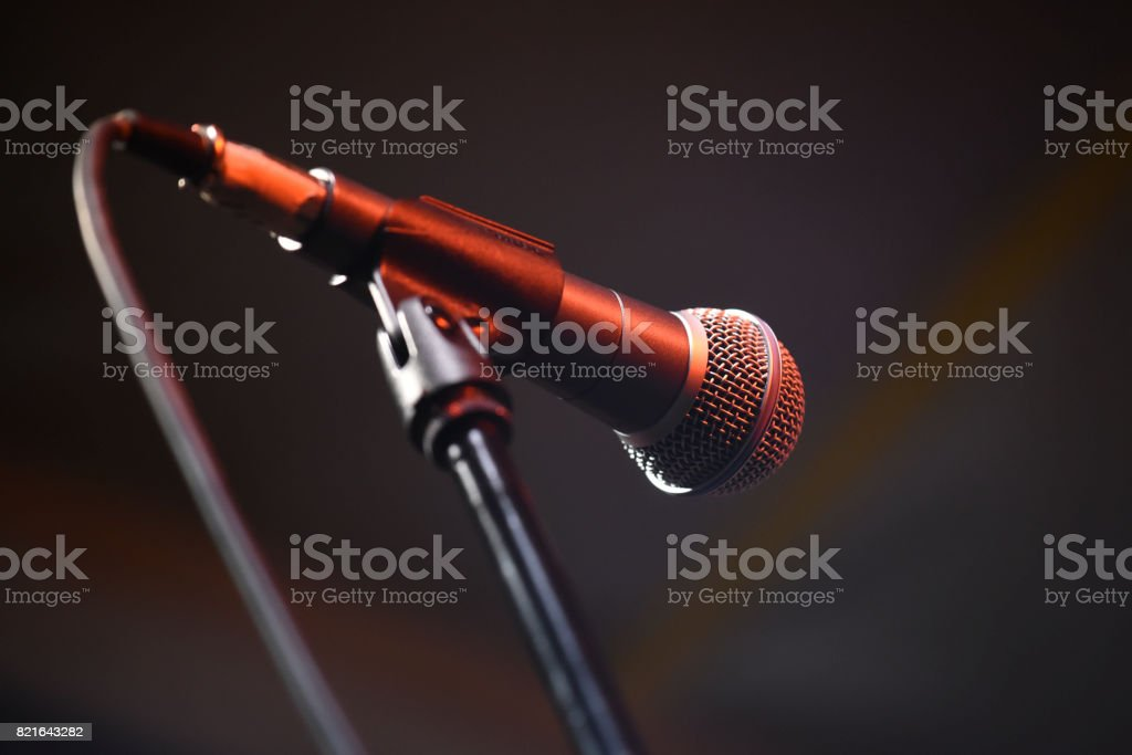 Microphone on the stage in red light on a music concert, dark background, stock photo