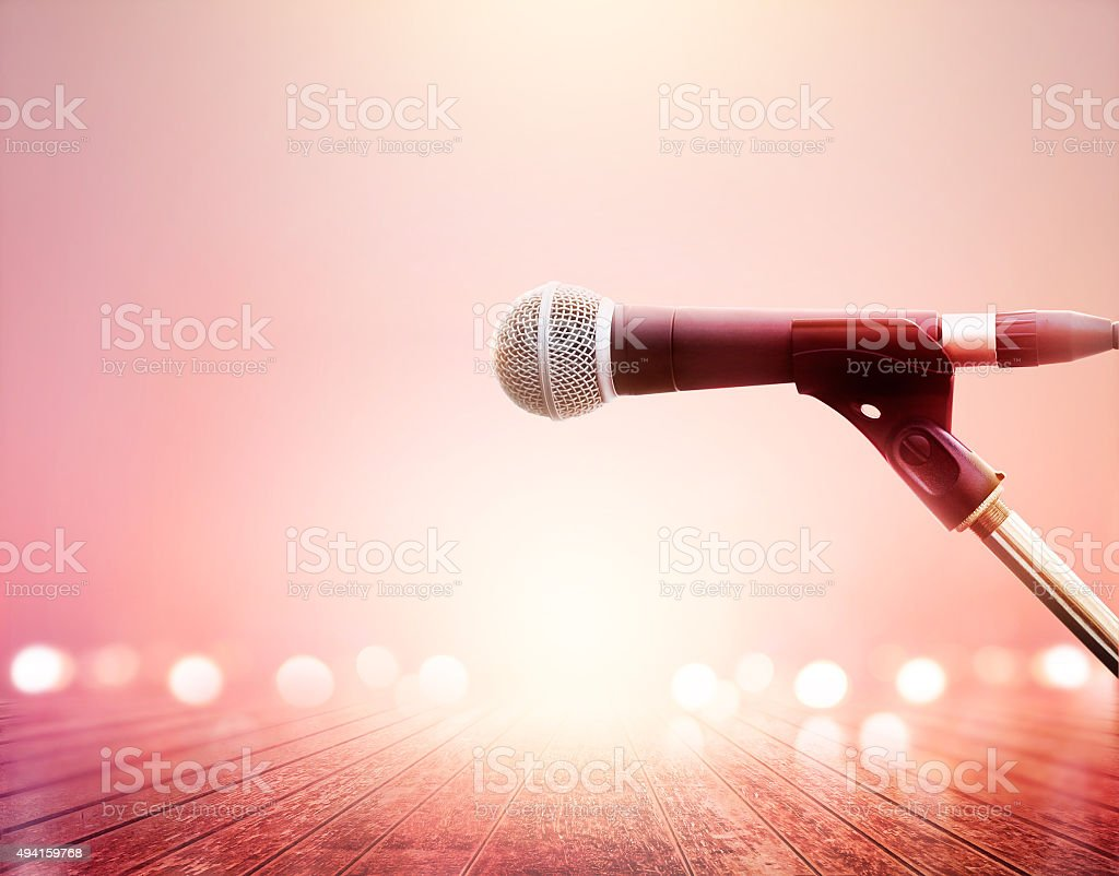 Microphone on vibrant lighting concert, wooden floor background stock photo