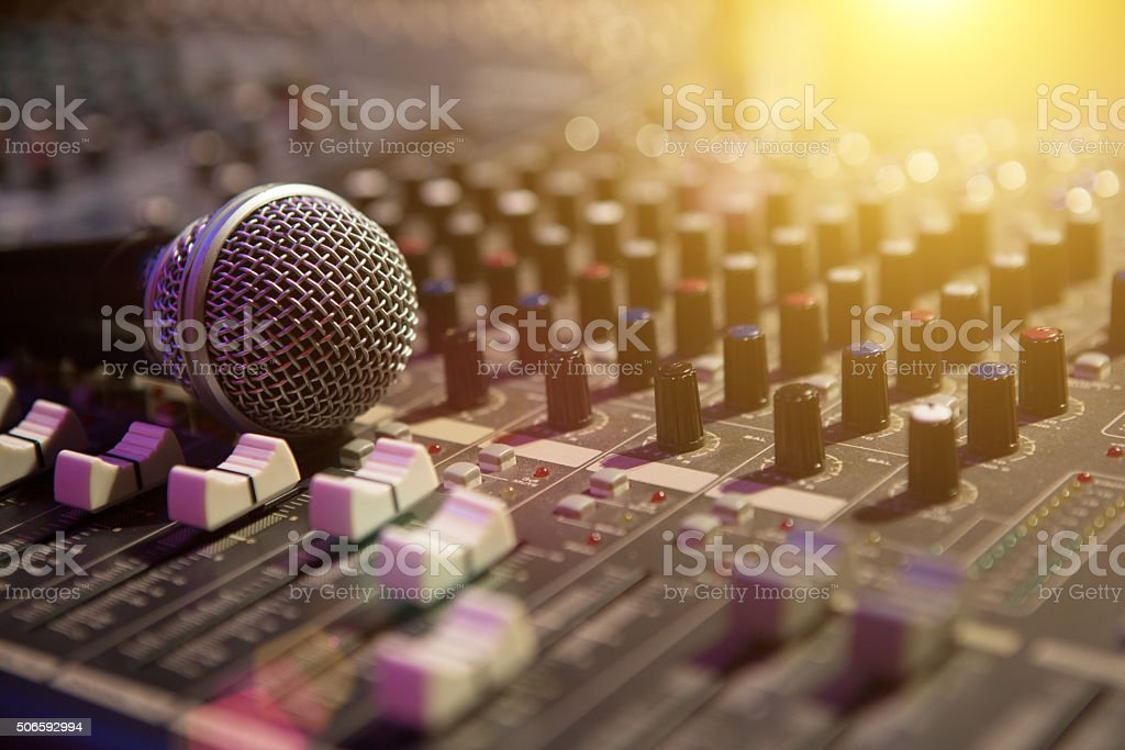 Microphone resting on a sound console stock photo