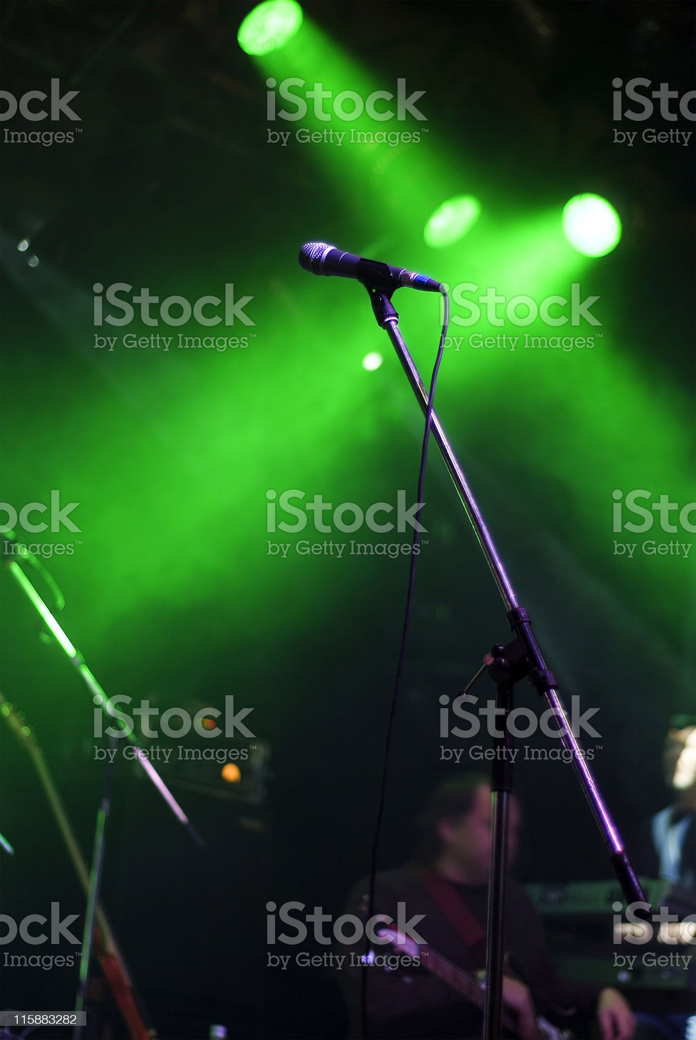 Microphone stand on green lit stage royalty-free stock photo